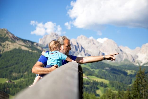 Padre e hijo mirando paisaje de montañas