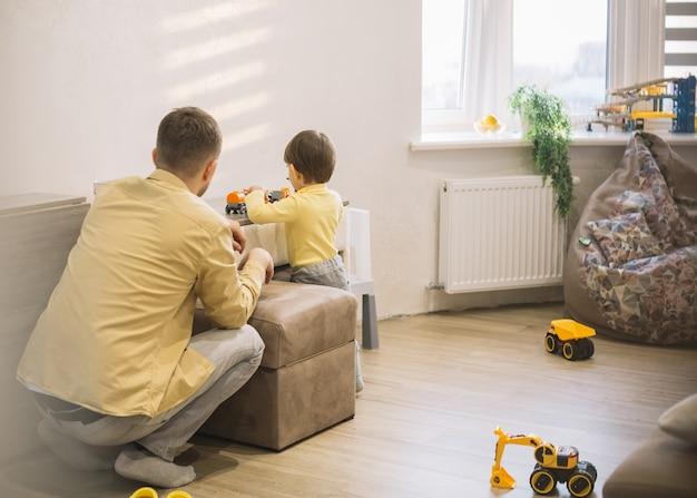 Padre e hijo en una moderna sala jugando