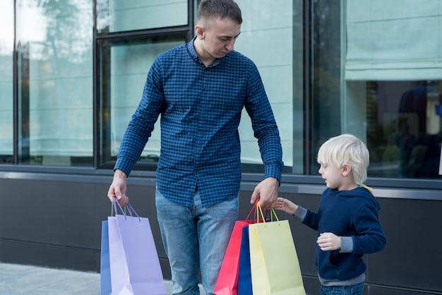 Padre e hijo pequeño con coloridos bolsos de compras en la calle.