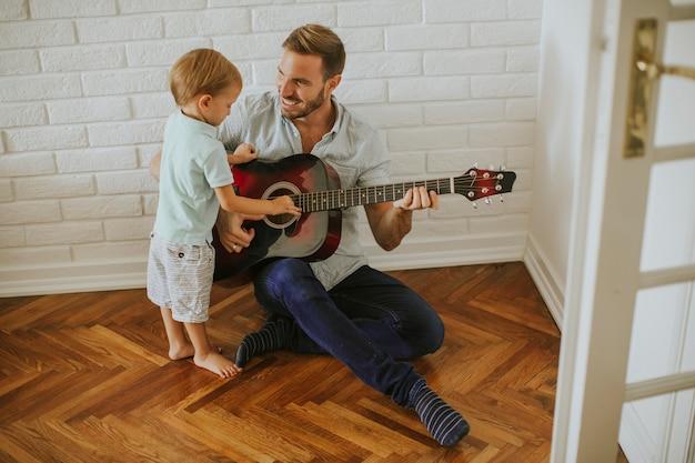Padre e hijo pequeño con guitarra.