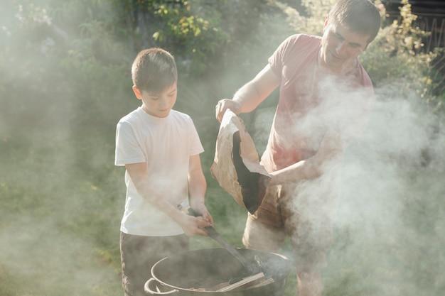 Padre e hijo poniendo carbón en barbacoa para preparar comida