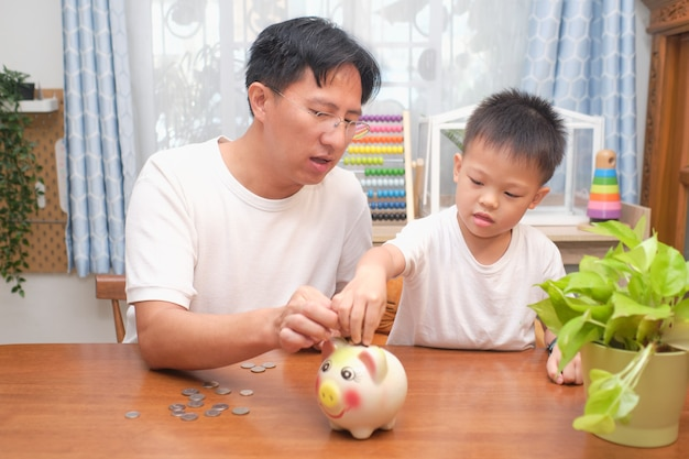 Padre e hijo poniendo monedas tailandesas en la alcancía en casa, concepto de ahorro de dinero de familia feliz