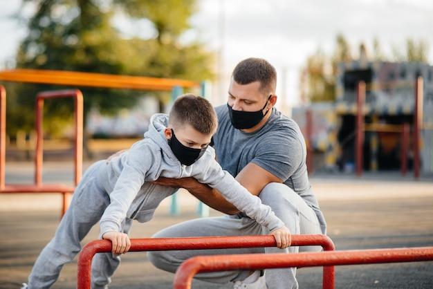 Padre e hijo practican deportes en el campo de deportes en máscaras durante la puesta de sol