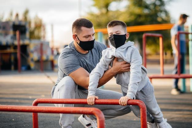 Padre e hijo practican deportes en el campo de deportes con máscaras durante la puesta de sol.
