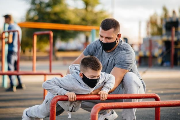 Padre e hijo practican deportes en el campo de deportes con máscaras durante la puesta de sol