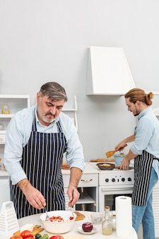 Padre e hijo preparando deliciosa ensalada