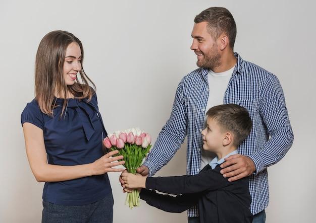 Padre e hijo regalando flores a mamá
