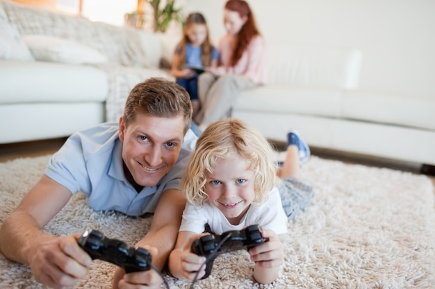 Padre e hijo en la sala de estar jugando videojuegos