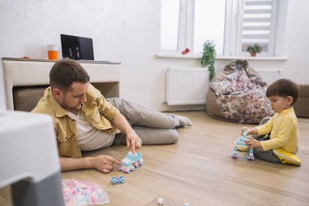 Padre e hijo en la sala de estar vista larga