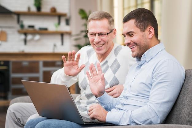 Padre e hijo saludando a alguien en video llamada