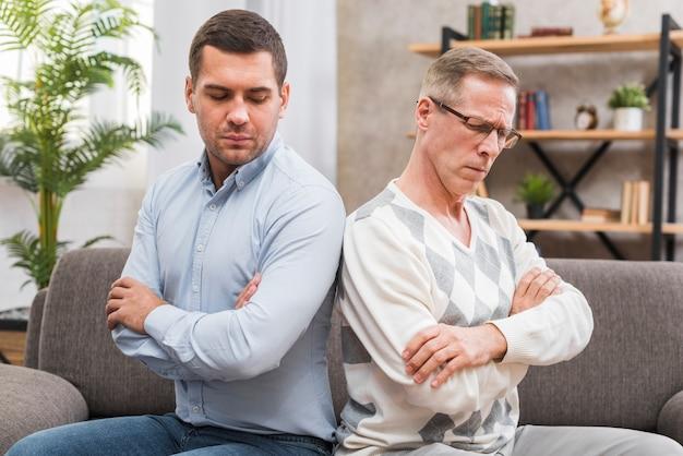 Padre e hijo sentados espalda con espalda