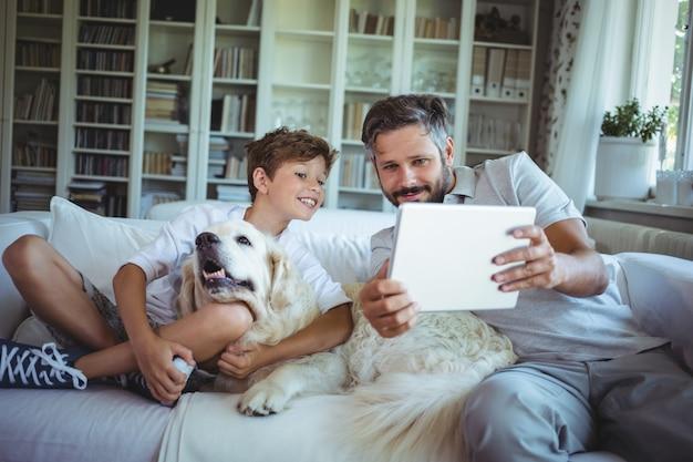 Padre e hijo sentados en el sofá con una mascota y usando tableta digital