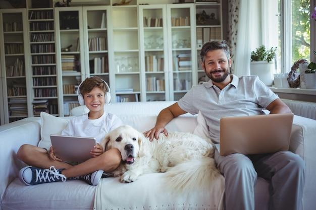 Padre e hijo sentados en el sofá y usando tableta digital y portátil