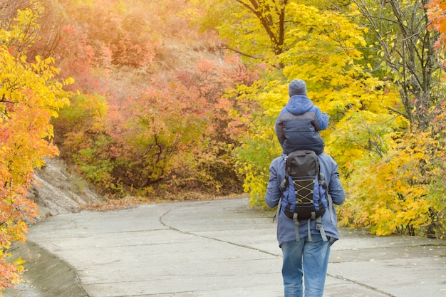 Padre e hijo sobre sus hombros caminan por el parque de otoño. vista trasera