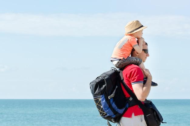 Padre e hijo sobre sus hombros se paran en la orilla del mar. vista lateral