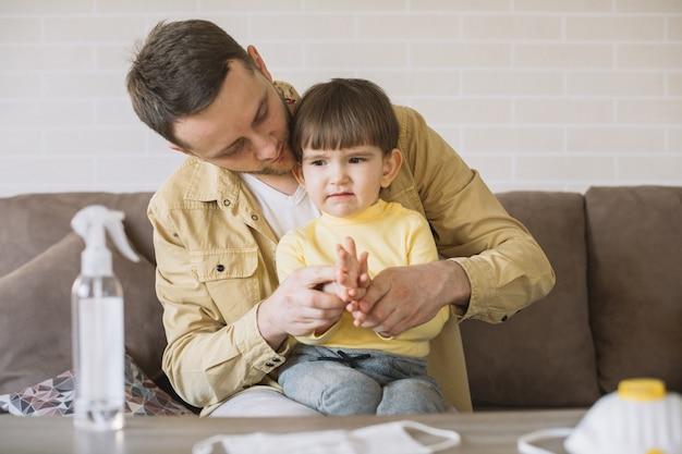 Padre e hijo en el sofá y máscaras médicas en la mesa