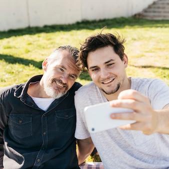 Padre e hijo sonrientes haciendo selfie