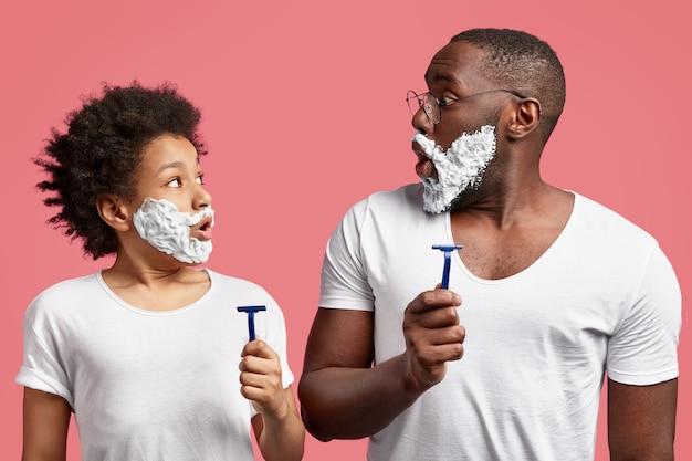 Padre e hijo sorprendidos con crema de afeitar en la cara, sujetan las navajas, sorprendidos porque no tienen tiempo para la higiene matutina