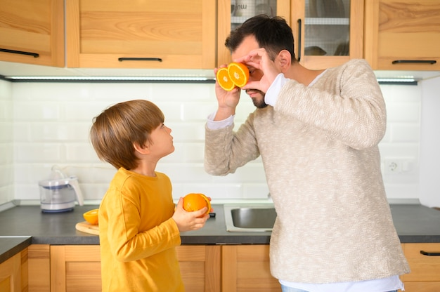 Padre e hijo sosteniendo mitades de naranjas