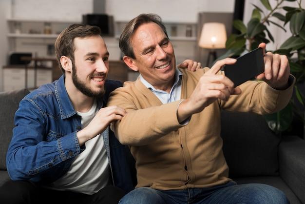 Padre e hijo tomando selfie en sala de estar