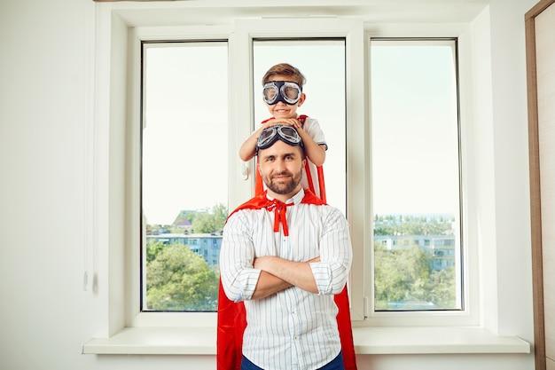 Padre e hijo en la ventana de la habitación.