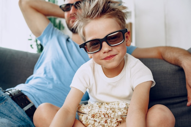 Padre e hijo viendo películas en casa con gafas 3d y comiendo palomitas de maíz en el sofá