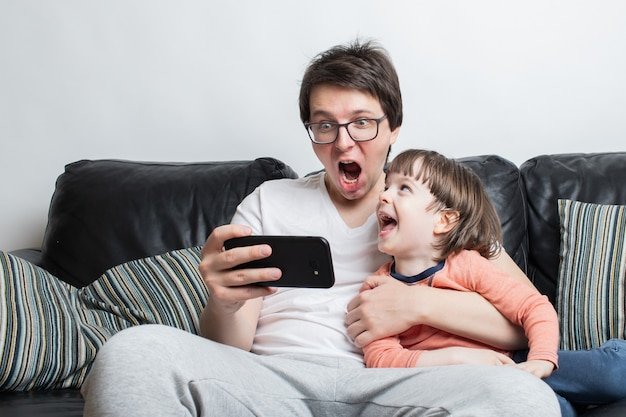 Padre e hijo viendo un video de miedo en el teléfono.