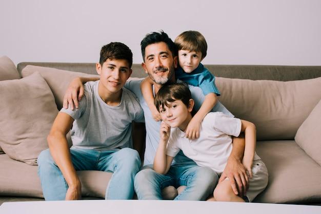 Padre e hijos en sofá en el día del padre