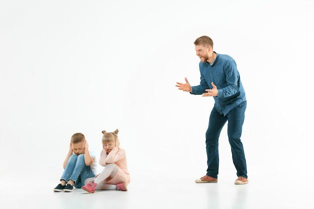 Padre enojado regañando a su hijo e hija en casa.