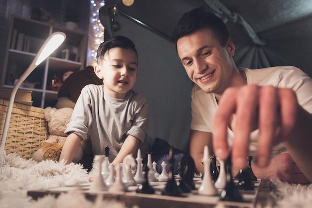 El padre enseña al pequeño hijo a jugar ajedrez en la noche en casa.