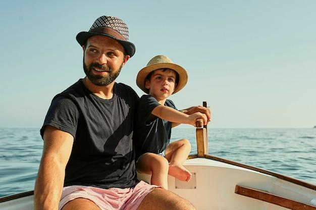 Un padre enseña a navegar a su hijo en un barco clásico.