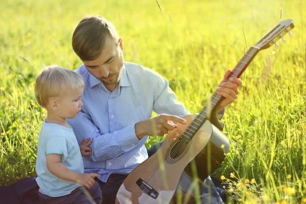 Padre enseña a su hijo a tocar la guitarra. tiempo juntos padre e hijo.