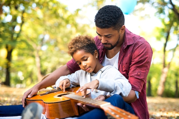 Padre enseñando a su adorable hija a tocar la guitarra en el parque