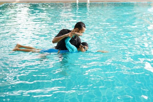 Padre enseñando a su hija a nadar en una piscina