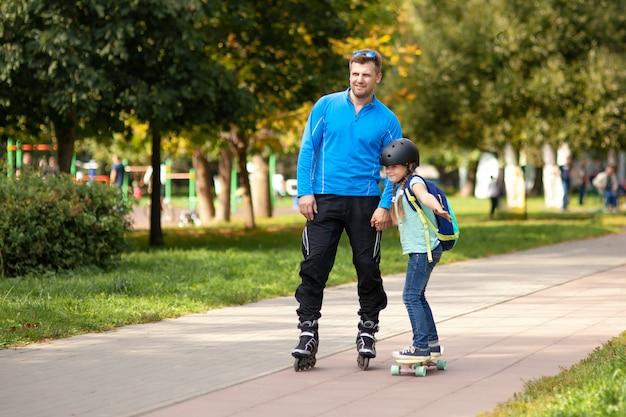 Padre enseñando a su hija a patinar