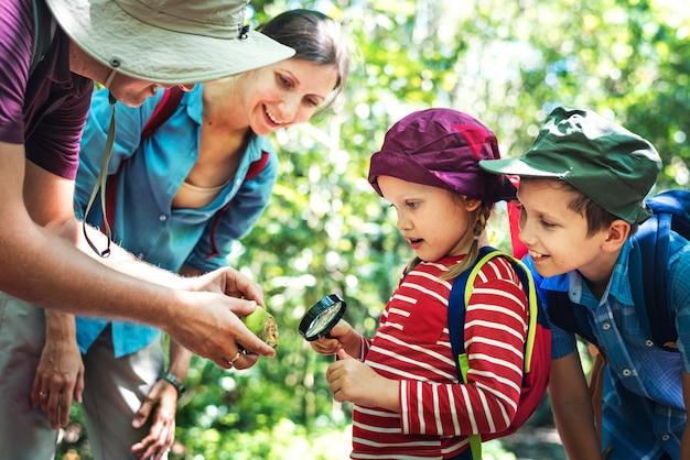 Padre enseñando a su hija a usar una lupa.