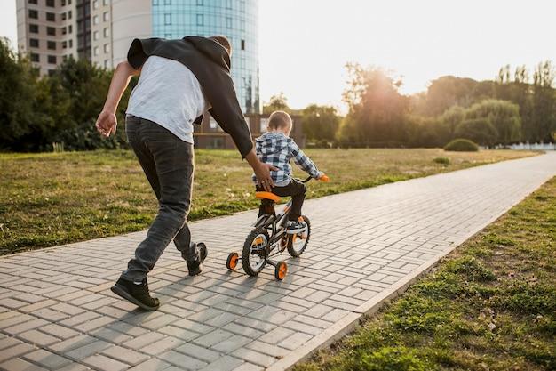 Padre enseñando a su hijo a andar en bicicleta