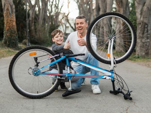 Padre enseñando a su hijo arreglando la bicicleta en el parque