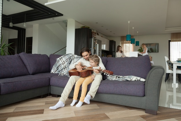 Padre enseñando a su hijo tocar guitarra, hija ayudando a su madre en la cocina