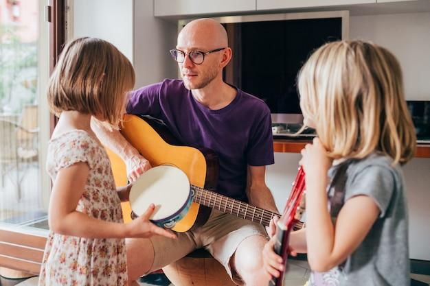 Padre enseñando a sus hijas a tocar la guitarra y tocar instrumentos