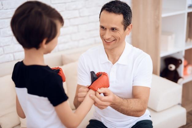 El padre está entrenando a su hijo boxeo.