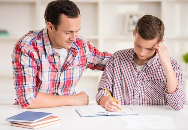Padre feliz ayudando a su hijo a hacer la tarea.
