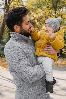 Padre feliz con bebé afuera en la naturaleza