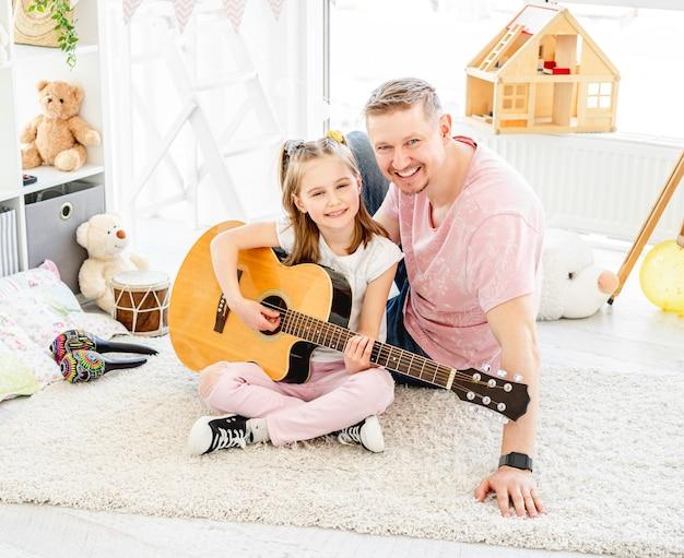 Padre feliz con hija alegre tocando la guitarra en la habitación de los niños