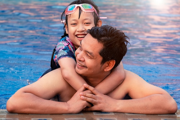 Padre feliz con hija pequeña en la piscina en el parque acuático con una sonrisa