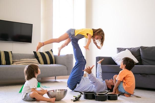Padre feliz con hija en las piernas y acostado en la alfombra. niños caucásicos alegres jugando en la sala de estar con papá. dos chicos guapos sentados en el suelo. concepto de actividad de infancia, vacaciones y juegos.
