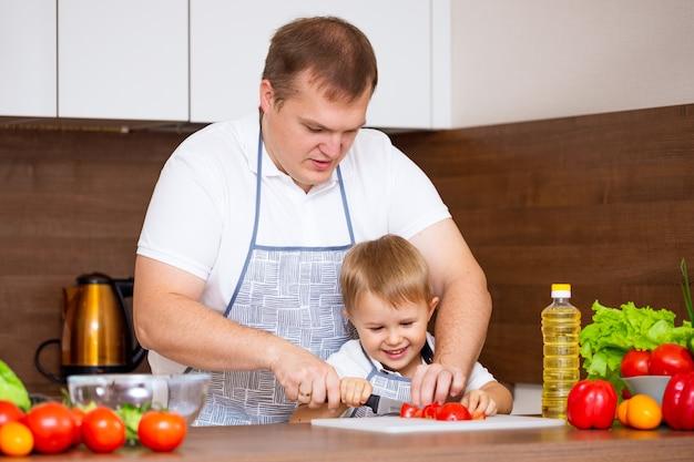 Un padre feliz y un hijo pequeño preparan una ensalada en la cocina con verduras. mi papá me enseña a cortar tomates en una pizarra. concepto de comida dietética
