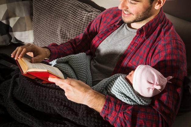 Padre feliz con el libro de lectura del bebé en la noche