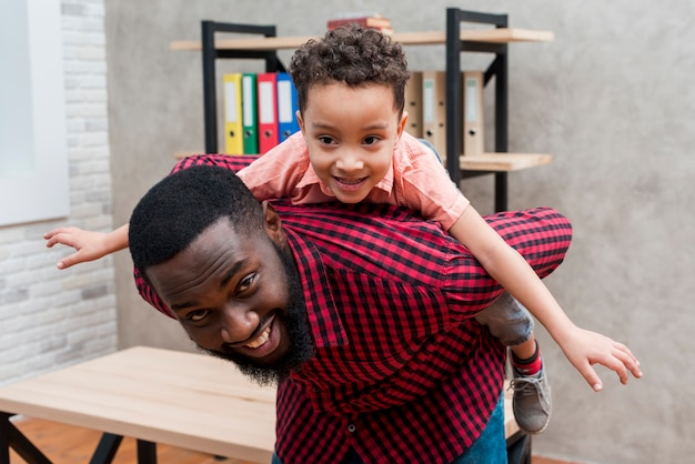Padre feliz negro llevando a hijo en la espalda