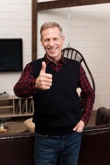 Padre feliz que presenta mientras que da los pulgares para arriba